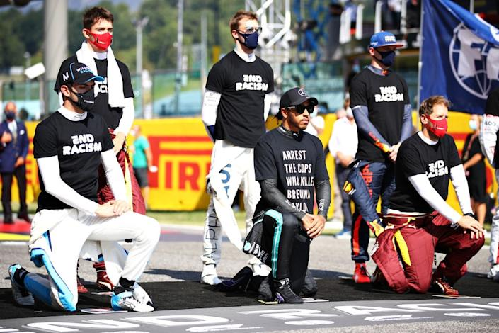 SCARPERIA, ITALY – SEPTEMBER 13: Nicholas Latifi of Canada and Williams, Lewis Hamilton of Great Britain and Mercedes GP and Sebastian Vettel of Germany and Ferrari kneel as Max Verstappen of Netherlands and Red Bull Racing, Daniil Kvyat of Russia and Scuderia AlphaTauri and Charles Leclerc of Monaco and Ferrari stand in support of ending racism before the F1 Grand Prix of Tuscany at Mugello Circuit on September 13, 2020 in Scarperia, Italy. (Photo by Mark Thompson/Getty Images)