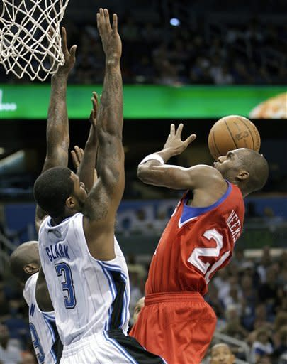 Philadelphia 76ers' Jodie Meeks, right, gets off a shot over Orlando Magic's Earl Clark (3) during the first half of an NBA basketball game, Monday, April 16, 2012, in Orlando, Fla. (AP Photo/John Raoux)