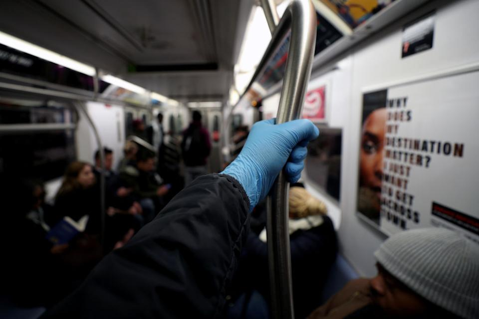 A man wears surgical gloves to prevent Covid-19 spread, at the New York City subway train in New York.