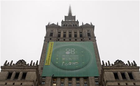 """Greenpeace activists fix a banner on the Palace of Culture and Science demanding protection of the Arctic region and the release of the so-called """"Arctic 30"""" group during the 19th conference of the United Nations Framework Convention on Climate Change (COP19) in Warsaw November 21, 2013. REUTERS/Kacper Pempel"""