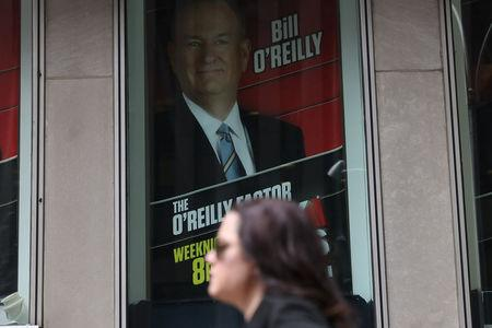 A woman walks by a sign showing Fox News Channel TV anchor Bill O'Reilly outside the News Corporation headquarters in New York City, in New York, U.S. April 19, 2017. REUTERS/Shannon Stapleton