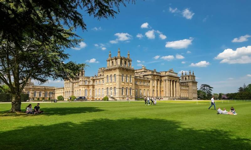 Blenheim Palace visitors relaxing on the lawn on a sunny day. The historic venue will host drive-in movies this summer.