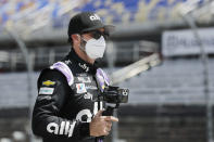 Driver Jimmie Johnson carries a camera as he walks to his car for the start of the NASCAR Cup Series auto race Sunday, May 17, 2020, in Darlington, S.C. (AP Photo/Brynn Anderson)
