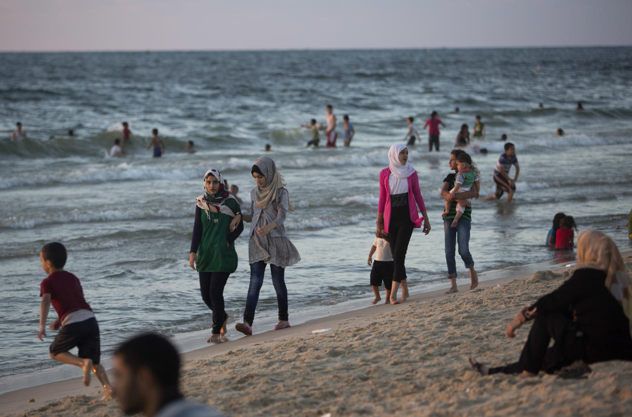 In this Saturday, Sept. 13, 2014 photo, Palestinians enjoy a summer sunset on the beach of Gaza City, Gaza Strip. After a ruinous war, Gaza is rushing back to a veneer of normalcy at astonishing speed. Street cafes and beaches are packed with people until late at night. Families crowd the few public parks. Wedding halls are booked solid. Far from a celebration, however, Gazans themselves acknowledge the revelry is only to thinly mask trauma and widespread despair (AP Photo/Khalil Hamra)