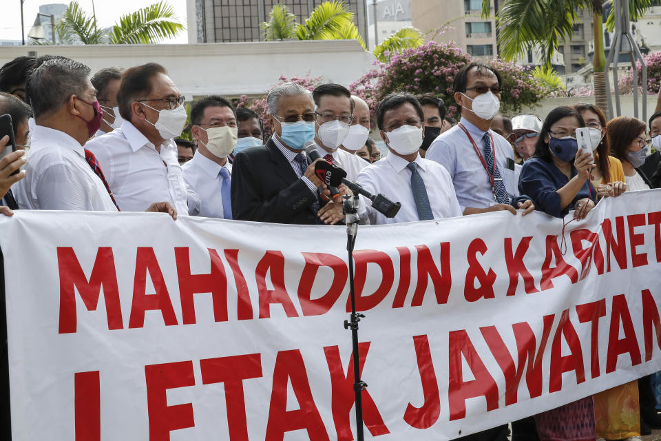 """Malaysian opposition members Anwar Ibrahim, third from left, and Mahathir Mohamad, fifth from left, speak to the media during a protest in Kuala Lumpur, Malaysia, Monday, Aug. 2, 2021. Malaysian opposition lawmakers marched toward the parliament building in Kuala Lumpur to demand Prime Minister Muhyiddin Yassin to resign. The banner reads: """"Muhyiddin and Cabinet resign."""" (AP Photo/FL Wong)"""