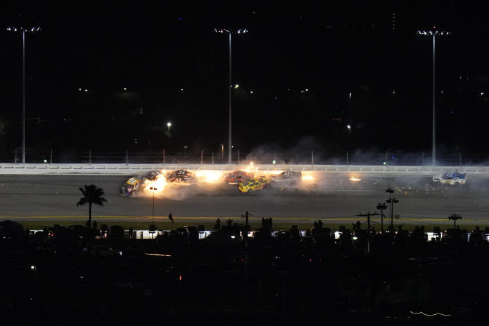 Racers crash during the last lap in the NASCAR Daytona 500 auto race at Daytona International Speedway, Monday, Feb. 15, 2021, in Daytona Beach, Fla. Among the driver involved were Kyle Busch (18); Brad Keselowski (2), who was in second before the crash; Joey Logano (22), who was leading; and Bubba Wallace (23). (AP Photo/Chris O'Meara)