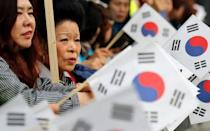 Supporters hold South Korean flags while waiting for a convoy transporting South Korean President Moon Jae-in to leave the Presidential Blue House for the inter-Korean summit, in Seoul, South Korea, April 27, 2018. REUTERS/Jorge Silva