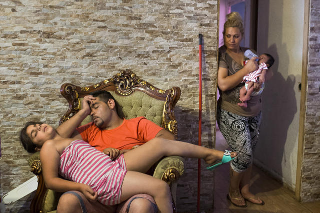 <p>Fernando Montoya Jimenez's son Manuel, 35, and his daughter rest after being awake all night during Fernando's eviction in Madrid, July 23, 2014. (AP Photo/Andres Kudaki) </p>