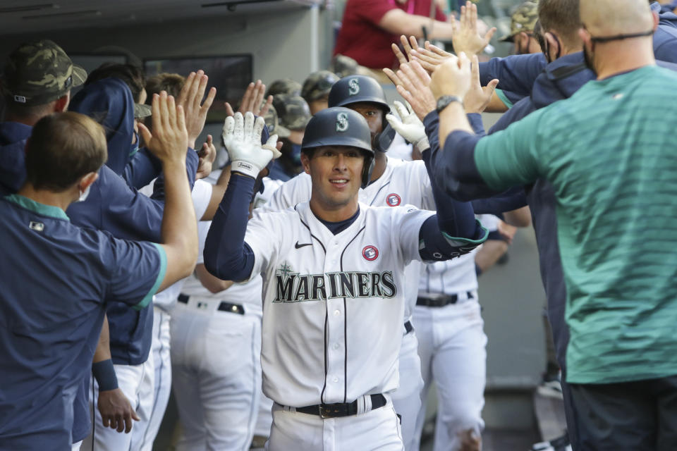 Seattle Mariners' Dylan Moore celebrates in the dugout after his three-run home run during the fourth inning of the team's baseball game against the Cleveland Indians, Saturday, May 15, 2021, in Seattle. (AP Photo/Jason Redmond)