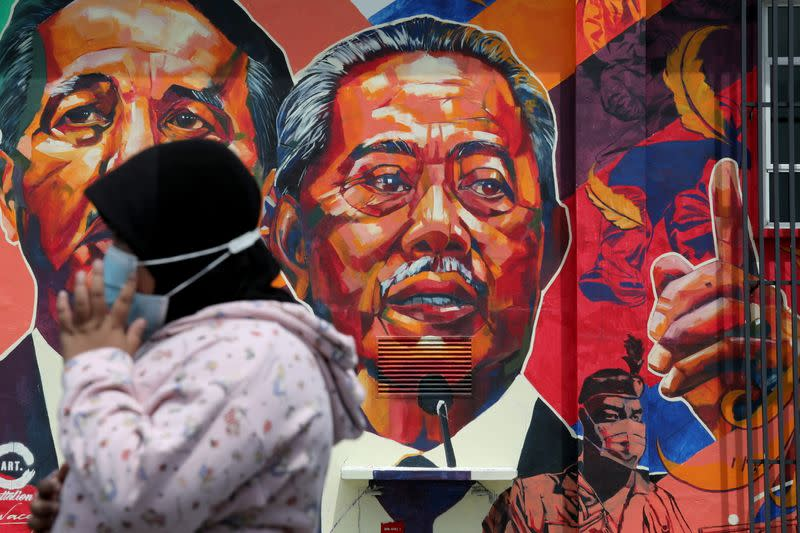 A woman passes by a mural depicting Malaysia's Prime Minister Muhyiddin Yassin in Kuala Lumpur