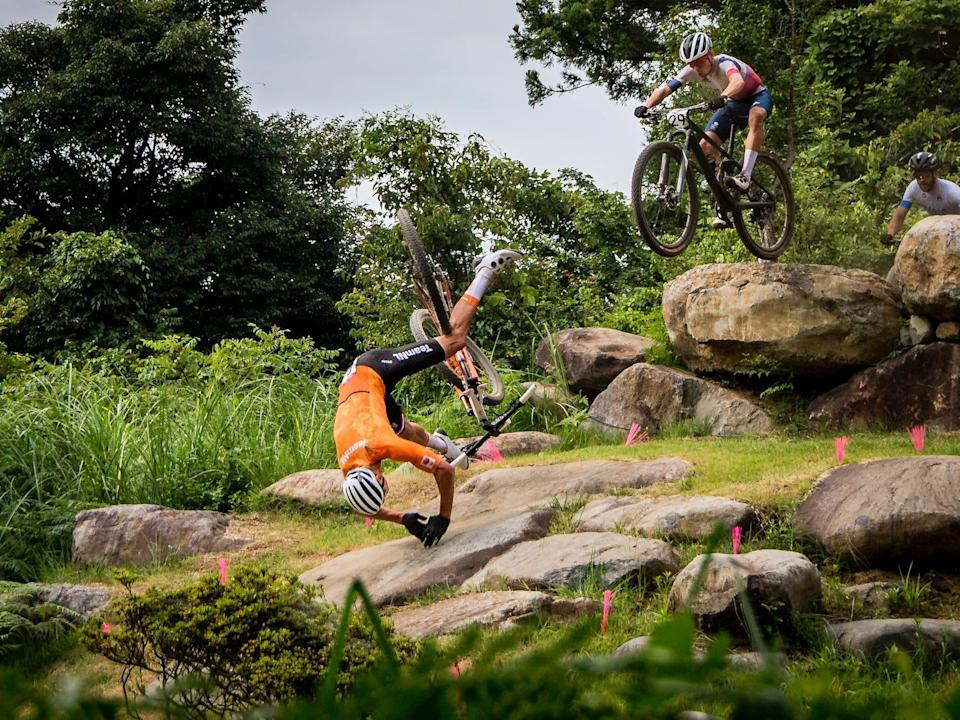 Mathieu Van der Poel falls off his bike over some rocks at the Tokyo Olympics.