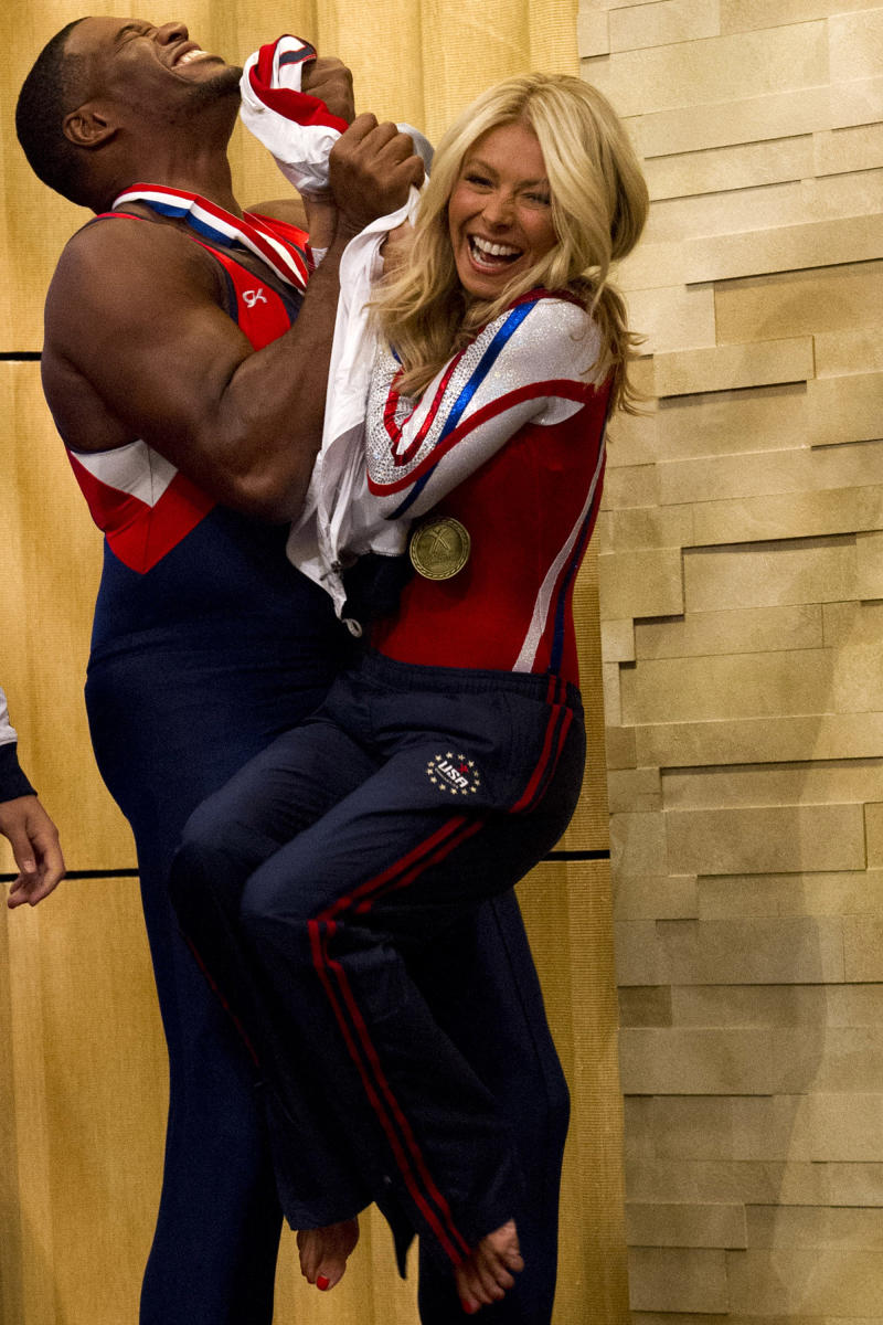 "Former football player Michael Strahan, left, jokes with Kelly Ripa on the set of the newly named ""Live! with Kelly and Michael"" on Tuesday, Sept. 4, 2012 in New York. Strahan joined the popular morning show as a permanent co-host on Tuesday, fulfilling a joking prophecy he made to Regis Philbin more than four years ago. The gap-toothed former New York Giant jogged onto the morning show set and picked up co-host Kelly Ripa in a bear hug, lifting her off her feet. He replaces Philbin, who left last November. Strahan was the survivor in a series of on-air tryouts of potential co-hosts since Philbin left, and his hiring has been an open secret for the past two weeks. (Photo by Charles Sykes/Invision/AP Images)"