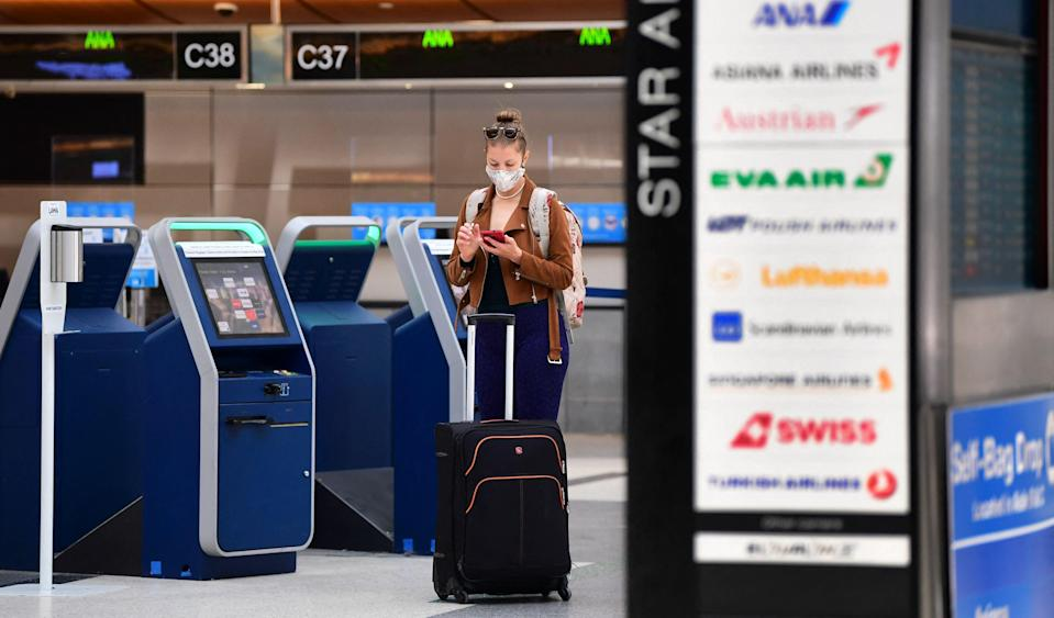<p>A woman checks her cellphone by self check-in kiosks on the departures level of Los Angeles International Airport (LAX) on May 27, 2021 in Los Angeles.</p> (AFP via Getty Images)