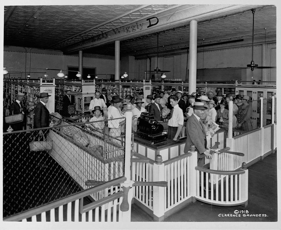"""<p>Customers make their way through the checkout line at a local Piggly Wiggly store. The grocery chain <a href=""""https://www.pigglywiggly.com/about-us"""" rel=""""nofollow noopener"""" target=""""_blank"""" data-ylk=""""slk:first opened its doors"""" class=""""link rapid-noclick-resp"""">first opened its doors</a> in 1916, with a store in Memphis, Tennessee. </p>"""