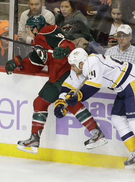Nashville Predators' Eric Nystrom, right, checks Minnesota Wild's Jared Spurgeon into the boards in the first period of an NHL hockey game, Tuesday, Oct. 22, 2013, in St. Paul, Minn. (AP Photo/Jim Mone)