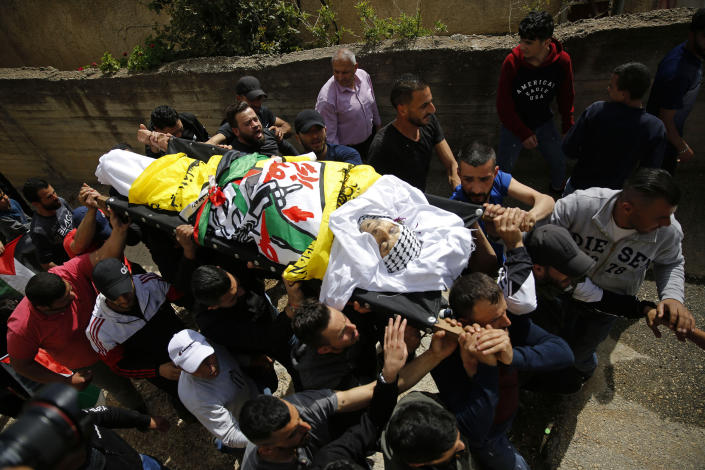 FILE - In this April 6, 2021 file photo, Palestinians carry the body of Osama Mansour who was killed by Israel soldiers at a temporary vehicle checkpoint in the occupied West Bank near Jerusalem, during his funeral, in the village of Biddu near the West Bank city of Ramallah. Somaya, Mansour's wife, who was in the car with her husband and was wounded by the gunfire, said they followed the soldiers' instructions and posed no threat. The shooting death has revived criticism of the Israeli military's use of deadly force. (AP Photo/Majdi Mohammed, File)