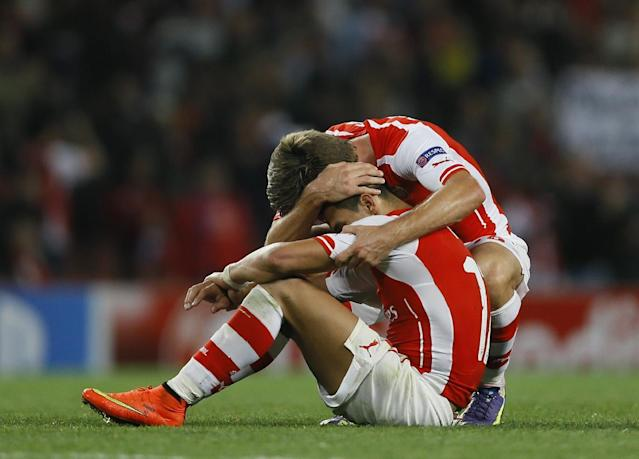 Arsenal's Mathieu Flamini, right, hugs teammate Alexis Sanchez at the end of their second leg Champions League qualifying soccer match between Arsenal and Besiktas at Emirates Stadium in London Wednesday, Aug. 27, 2014.(AP Photo/Kirsty Wigglesworth)