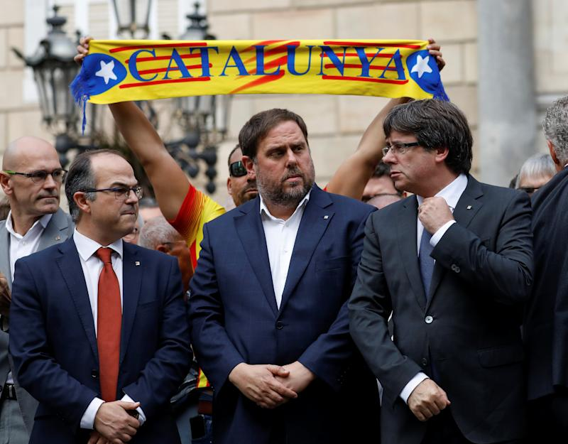Catalan President Carles Puigdemont (R) and other regional government members stand with people in Plaza Sant Jaume. (Reuters)
