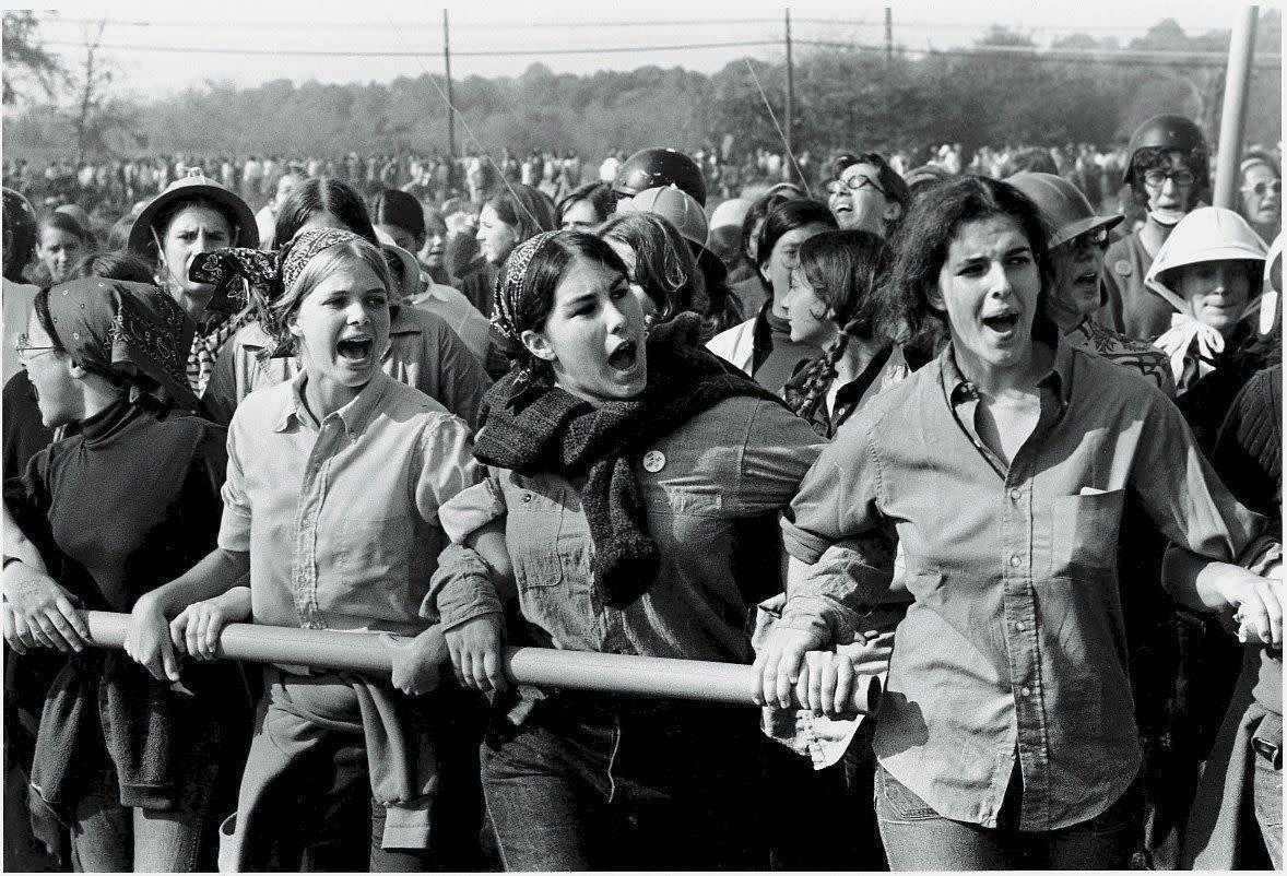A group of young women have arms interlocked as they hold a metal pipe and protest the Vietnam War at Fort Dix, a major transshipment point for American soldiers, Fort Dix, New Jersey, October 12, 1969.