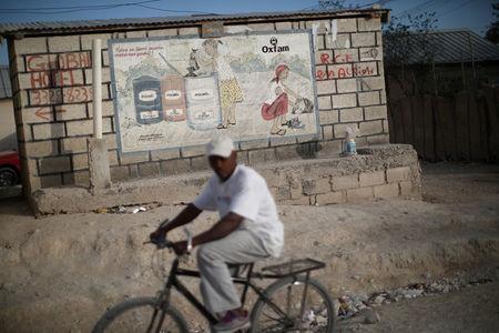 A man rides a bike next to an Oxfam sign in Corail, a camp for displaced people of the 2010 earthquake, on the outskirts of Port-au-Prince, Haiti, February 13, 2018. REUTERS/Andres Martinez Casares