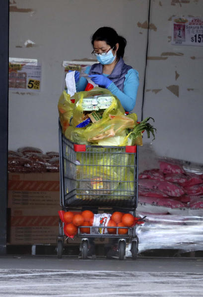Wearing a mask amid concerns of the spread of COVID-19, a woman checks her receipt after shopping for groceries in Richardson, Texas, Wednesday, April 1, 2020. (AP Photo/LM Otero)