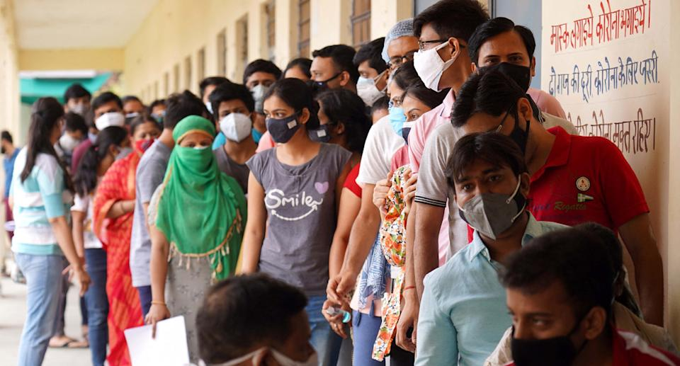 A photo shows vaccine queue in India on Sunday.