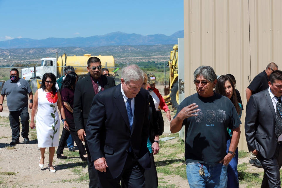 Wastewater manager Nelson Edmonds speaks with Agriculture Secretary Tom Vilsack about his dilapidated facility on Wednesday, July 7, 2021, in Ohkay Owingeh, New Mexico. Vilsack announced that the Pueblo will receive a $610,000 loan and a $1.6 million grant in state money to expand the wastewater treatment plant where Edmonds works. Edmonds says some of the equipment at the plant in rusting through. (AP Photo/Cedar Attanasio)