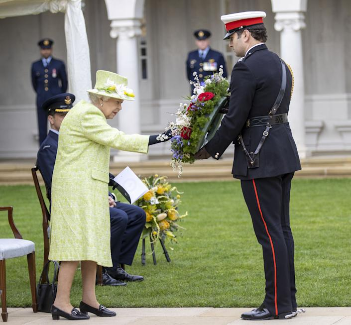 Queen Elizabeth II inspects a wreath before it was laid by her equerry for her. (PA Images)
