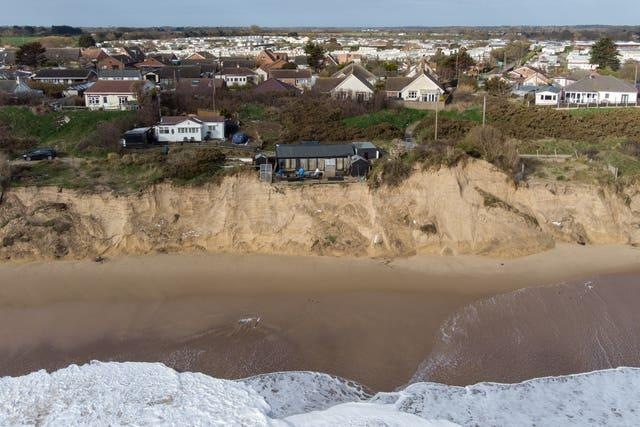 Former soldier Lance Martin, 63, stands in the back garden of his home in Hemsby, Norfolk, where his back door is now no more than six metres from the cliff edge after more land has been lost to the sea in the past few days