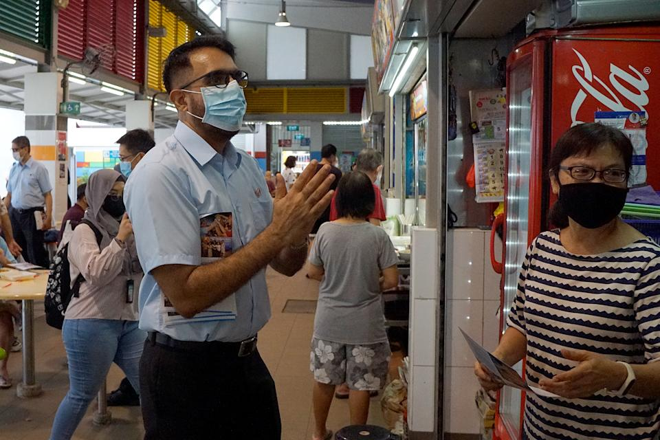 Workers' Party chief Pritam Singh speaking with a hawker during a party walkabout in Bedok North on 27 June 2020. (PHOTO: Dhany Osman / Yahoo News Singapore)