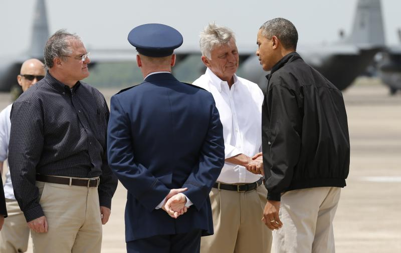 U.S. President Barack Obama is greeted by Arkansas Governor Mike Beebe (2nd R) and U.S. Senator Mark Pryor (L) upon his arrival in Little Rock, Arkansas May 7, 2014. Obama is in Arkansas to see the damage cause by recent tornadoes and meet with families and first responders. The tornadoes were part of a storm system that blew through the Southern and Midwestern United States earlier this week, killing at least 35 people, including 15 in Arkansas. Obama has already declared a major disaster in Arkansas and ordered federal aid to supplement state and local recovery efforts.REUTERS/Kevin Lamarque (UNITED STATES - Tags: POLITICS DISASTER)