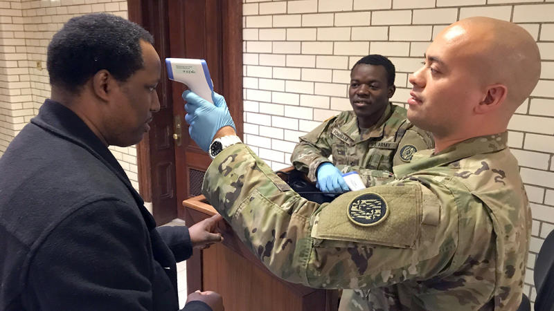 Journalist William J. Ford of The Washington Informer has his temperature read by Sgt. Jason Grant, right, of the Maryland National Guard as PFC Theophilus Foinmbam looks on Thursday, March 19, 2020 at the State House in Annapolis. Everyone entering the State House must go through a temperature screening, answer health questions, and provide a phone number. (Amy Davis./The Baltimore Sun via AP)