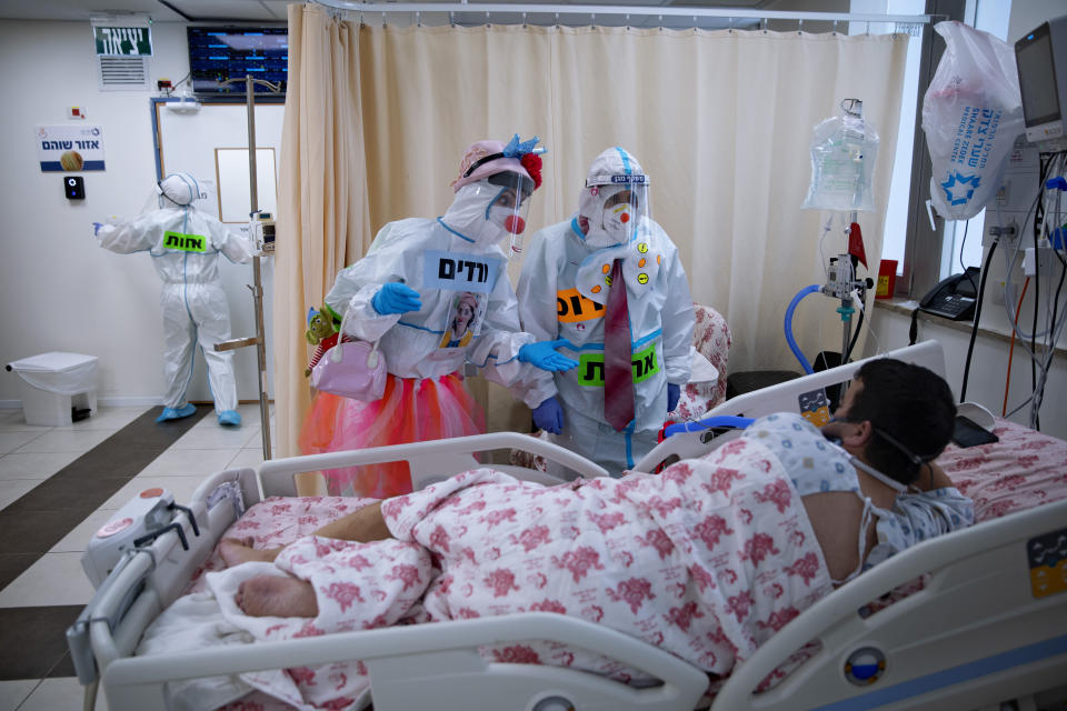 Clowns wearing protective equipment entertain a COVID-19 patient in the intensive care ward for coronavirus patients at Shaare Zedek Medical Center in Jerusalem, Monday, Nov. 23, 2020. (AP Photo/Oded Balilty)