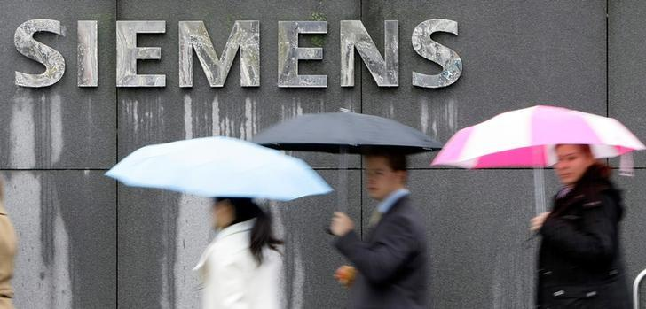 FILE PHOTO: People covered with umbrellas walk next to a Siemens building in Munich
