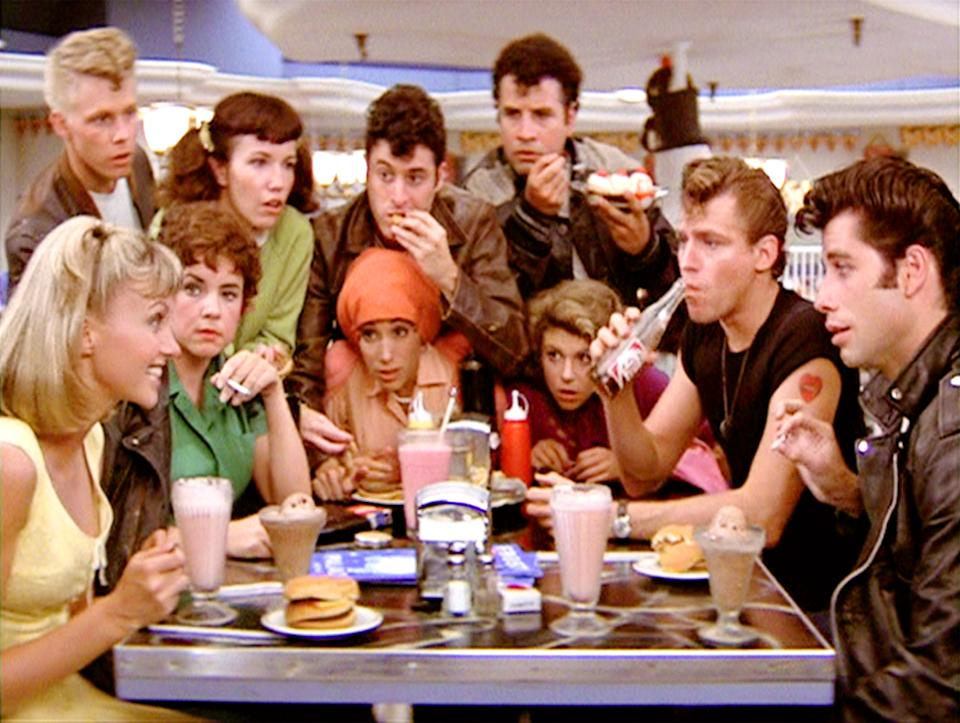 """LOS ANGELES - JUNE 16: The movie """"Grease"""", directed by Randal Kleiser. Seen here at the malt shop, the Pink Ladies and the T-Birds. In back from left, Kelly Ward (as Putzie), Jamie Donnelly (as Jan), Barry Pearl (as Doody) and Michael Tucci (as Sonny). Seated, from left, Olivia Newton-John (as Sandy), Stockard Channing (as Rizzo), Didi Conn (as Frenchy), Dinah Manoff (as Marty), Jeff Conaway (as Kenickie) and John Travolta (as Danny).Initial theatrical release of the film, June 16, 1978.Screen capture. Paramount Pictures. (Photo by CBS via Getty Images)"""