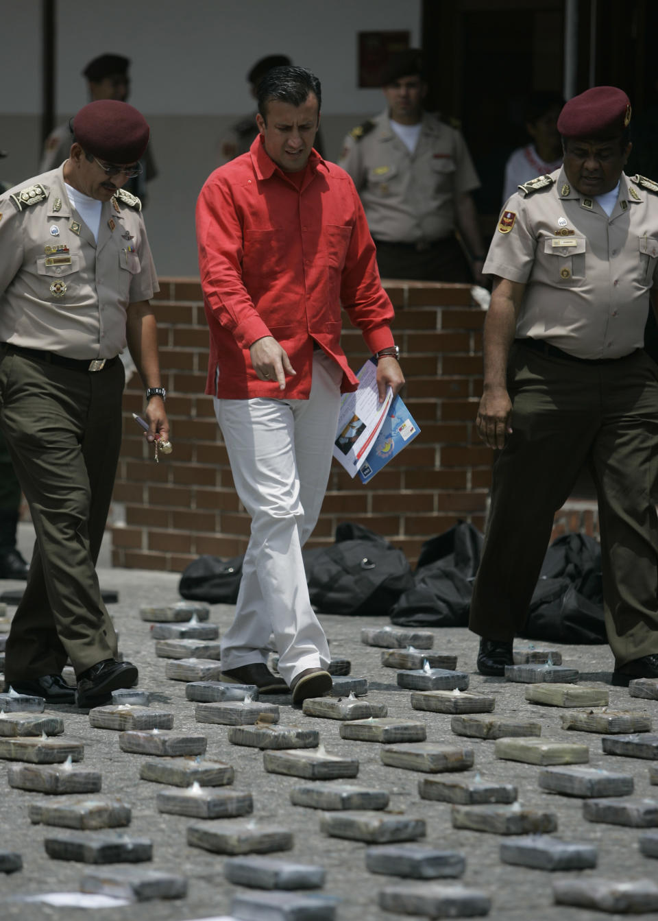 Justice Minister Tareck El Aissami, center,walks among packs of cocaine displayed at a military base in Puerto Cabello Venezuela, Monday, July  27, 2009. (AP: Ariana Cubillos)