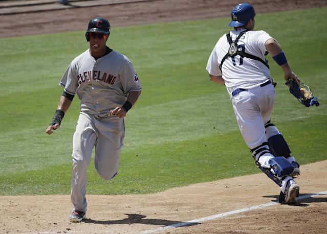 Cleveland Indians' Michael Brantley, left, runs toward home plate to score on a single hit by David Murphy as Los Angeles Dodgers catcher A.J. Ellis, right, goes after the throw during the eighth inning of a baseball game on Wednesday, July 2, 2014, in Los Angeles. (AP Photo/Jae C. Hong)