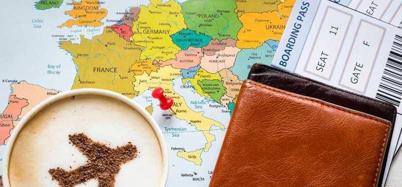 A map with a pin in it on Italy, covered by a boarding pass and a cup of coffee