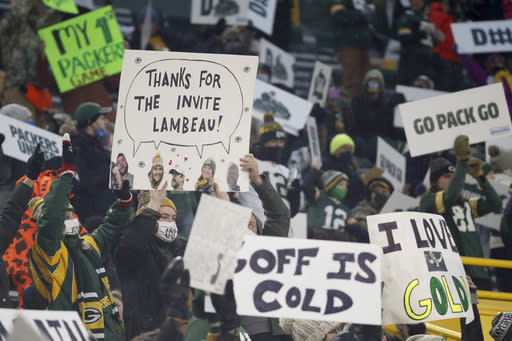 Packers' fans hold up signs during the first half of an NFL divisional playoff football game between the Green Bay Packers and the Los Angeles Rams Saturday, Jan. 16, 2021, in Green Bay, Wis. Spectators were allowed in Lambeau Field for the first time during this season. (AP Photo/Mike Roemer)