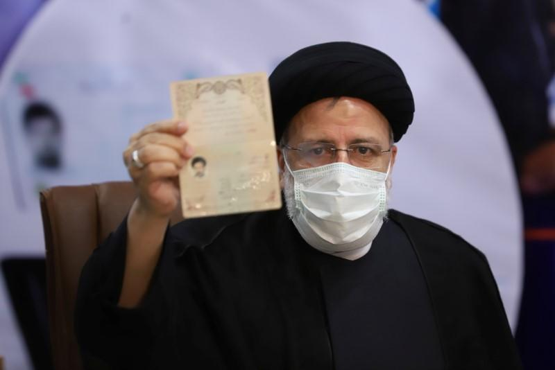 Ebrahim Raisi, Chief Justice of Iran, shows his identification document as he registers as a candidate for the presidential election at the Interior Ministry, in Tehran