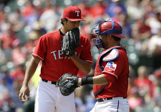 Texas Rangers' Yu Darvish, left, of Japan, talks with catcher Geovany Soto between pitches to the Oakland Athletics in the first inning of a baseball game, Saturday, Sept. 14, 2013, in Arlington, Texas. (AP Photo/Tony Gutierrez)