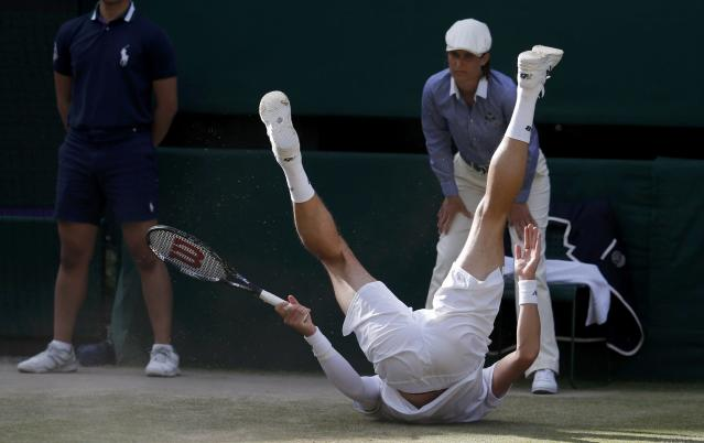 Milos Raonic of Canada falls during his men's singles semi-final tennis match against Roger Federer of Switzerland at the Wimbledon Tennis Championships, in London July 4, 2014. REUTERS/Suzanne Plunkett (BRITAIN - Tags: SPORT TENNIS)
