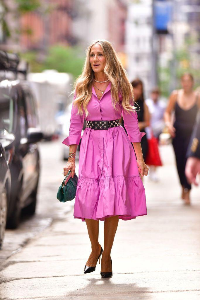 """<p>It's all so very Carrie! On another day of shooting And Just Like That on July 19 in the NoHo area of New York City, Parker wore a Carolina Herrera pink ruffled-hem shirt midi dress cinched at the waist with a vintage belt <a href=""""https://www.instagram.com/p/CRhdHGZNS2X/"""" rel=""""nofollow noopener"""" target=""""_blank"""" data-ylk=""""slk:which the most diligent SATC fans will recognise from the first movie."""" class=""""link rapid-noclick-resp"""">which the most diligent SATC fans will recognise from the first movie. </a></p><p>In classic Carrie fashion, she's wearing vintage Manolo Blahnik heels. </p>"""