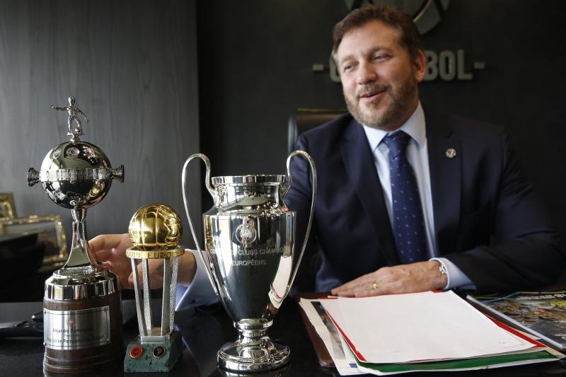 Conmebol President Alejandro Dominguez touches a Copa Libertadores trophy, left, next to UEFA and Champions League trophies, during an interview at the soccer organization's headquarters in Luque, Paraguay, Wednesday, Feb. 19, 2020. Domnguez expressed reservations with the new format set up for the FIFA club world championship recently announced by FIFA. (AP Photo/Jorge Saenz)