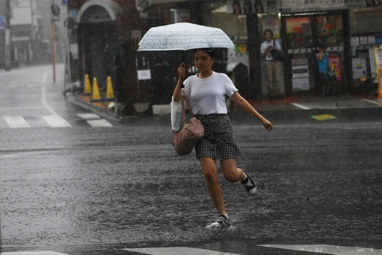 A woman runs across a street in heavy rain in Tokyo, brought by the powerful tropical storm