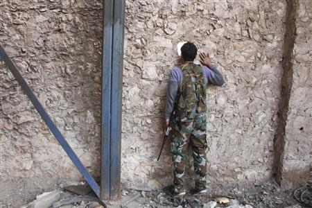A Fighter from Tawhid Brigade, which operates under the Free Syrian Army, looks through a hole in the wall in Base 80 area of Aleppo
