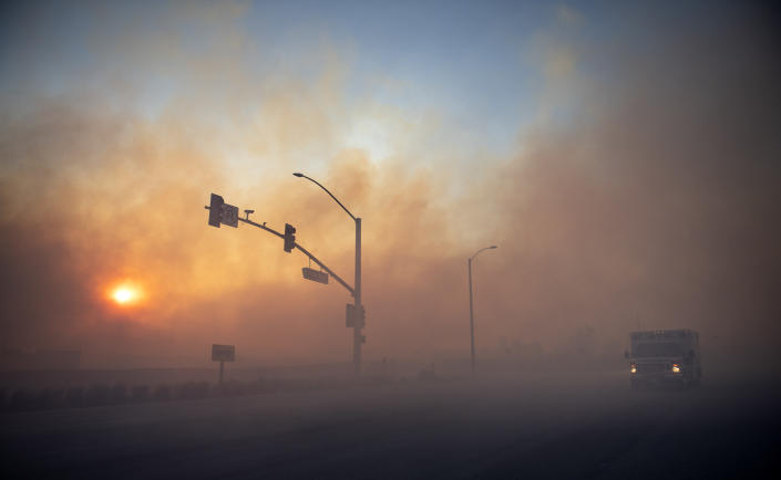 Early morning smoke casts an eerie orange cast along Irvine Blvd. near Alton on Tuesday, Oct. 27, 2020, because of (Mindy Schauer/The Orange County Register via AP)