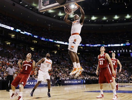Syracuse forward C.J. Fair (5) dunks in front of Wisconsin guards Ben Brust (1) and Josh Gasser (21) in the first half of an East Regional semifinal game in the NCAA men's college basketball tournament, Thursday, March 22, 2012, in Boston. (AP Photo/Elise Amendola)