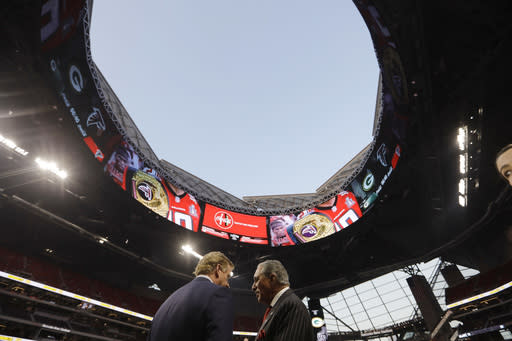 FILE - In this Sept. 17, 2017, file photo, NFL commissioner Roger Goodell, left, speaks with Atlanta Falcons owner Arthur Blank under the open roof before an NFL football game between the Atlanta Falcons and the Green Bay Packers in Atlanta. Nine months after Mercedes-Benz Stadium opened, what is being called the final construction phase of the facility's unique but problematic roof is set to begin on Tuesday, May 29, 2018. The goal is to complete the automation of the roof, allowing it to open and close in as little as 12 minutes. (AP Photo/David Goldman, File)