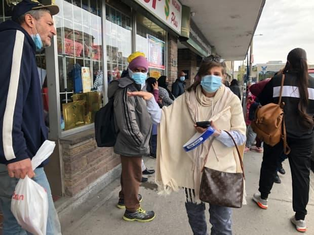 Stella Bailakis, who has been sharing COVID-19 information door-to-door for The Park Extension Round Table, joked with people in line and made sure they were over 45 to qualify for the vaccine.